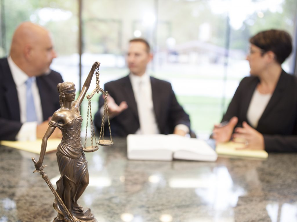 Picture of a lady justice statue in the foreground and the firm attorneys in the background